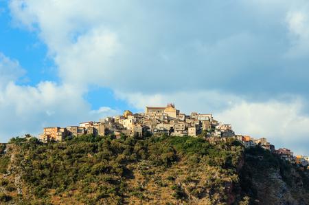 Opinión del verano de Calabria con el pueblo viejo hermoso en la cima de la colina de la montaña sobre la costa de mar tirreno, Italia. Foto de archivo - 94389802