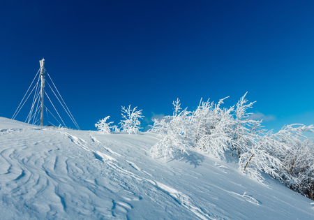 Beautiful winter rime frosting trees, communication tower and footpath through snowdrifts on mountain slope on blue sky background (Carpathian mountain, Ukraine)
