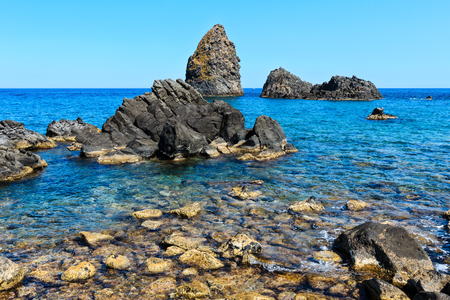 Cyclopean Coast and the Islands of the Cyclops on Aci Trezza town (Italy, Sicily,10 km north of Catania). Known as Isoles Dei Ciclopi Faraglioni.