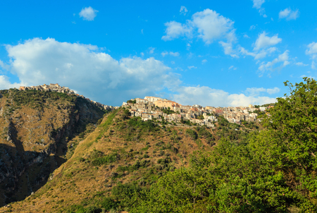 Calabria summer view with beautiful old village on mountain hill top above Tyrrhenian sea coast, Italy.