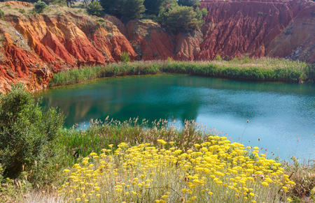 The lake in a old bauxites red soils quarry cave in Apulia, Otranto, Salento, Italy. The digging was filled with natural waters. Stock Photo
