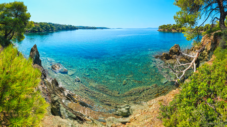 Morning summer Aegean Sea rocky coast landscape with pine trees on shore, Sithonia (near Ag. Kiriaki), Halkidiki, Greece. Four shots stitch high-resolution panorama.  Stock Photo