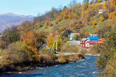 Autumn Carpathian mountain White Tysa river landscape with multicolored trees on slope and village (Transcarpathia, Ukraine).