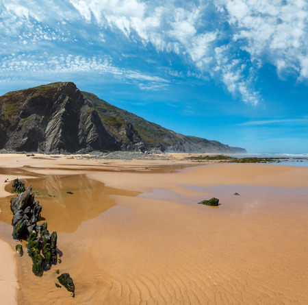 Rock formations on sandy beach and blue sky with cumulus clouds (Algarve, Costa Vicentina, Portugal). Two shots stitch image. Beautiful natural summer vacation travel concept.
