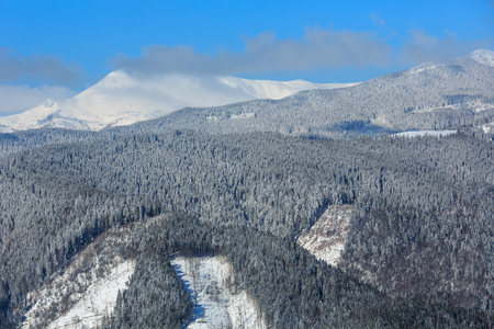Picturesque winter mountain view from Skupova mountain slope, Ukraine, view to Chornohora ridge and Pip Ivan mountain top in clouds, Carpathian.