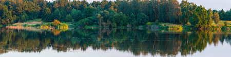 Evening summer lake high-resolution panorama landscape with beautiful trees reflections on water surface (near Shklo settlement, Lviv Oblast, Ukraine).