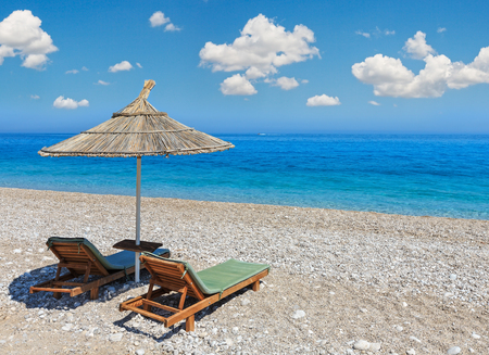 Summer morning sandy beach with sunbeds and strawy sunshade (Albania). Deep blue sky with some cumulus clouds. Stock Photo