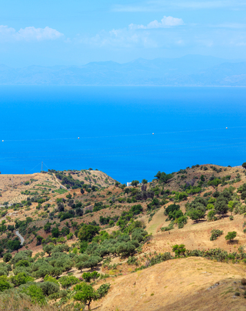 Picturesque summer view to sea and Sicily island in far from mountain hills in Motta San Giovanni outskirts, Reggio Calabria, Italy. Archivio Fotografico