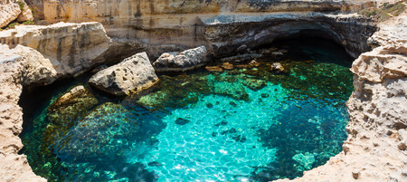 Picturesque seascape with white rocky cliffs, caves, sea bay and islets at Grotta della poesia, Roca Vecchia, Salento Adriatic sea coast, Puglia, Italy