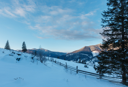 Sunrise morning winter mountain village outskirts. View from rural snow covered path on hill slope , Zelene, Verkhovyna Ukraine.