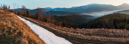 Early morning spring Carpathian mountains plateau landscape with snow-covered ridge tops in far, Ukraine. Stock Photo
