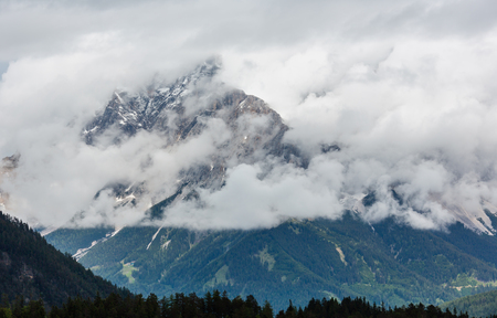 Summer overcast mountain top in clouds view from Fernpass, Austria, near Zugspitze mountain.