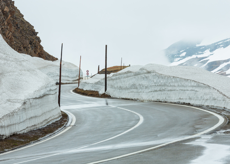 Spring cloudy overcast mountain landscape with serpentine road on Furka Pass, Switzerland.
