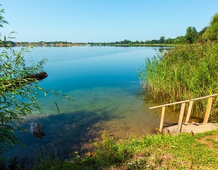 Picturesque summer lake calm beach with wooden stairs to the water. Concept of tranquil country life, eco friendly tourism, camping, fishing. Stock Photo