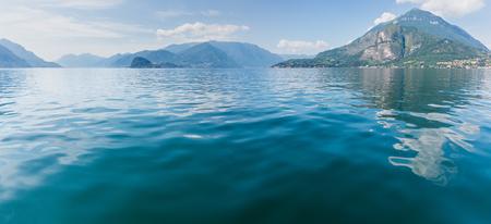 Lake Como (Italy) summer coast hazy view from ship board. Panorama.
