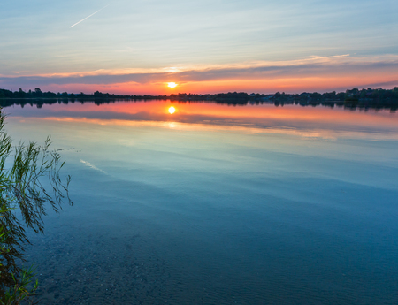 Picturesque summer evening sunset lake calm shore. Concept of tranquil country life, eco friendly tourism, camping, fishing. 免版税图像