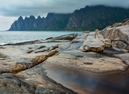 Stony beach with tidal baths at Ersfjord, Senja, Norway. Summer polar day night coast. The dragon teeth rock in far.