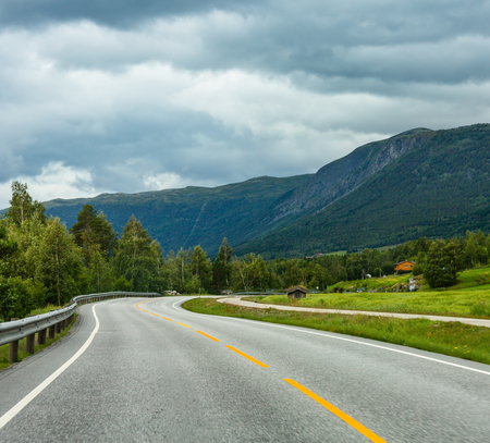 Summer cloudy mountain landscape with serpentine secondary road, Norway