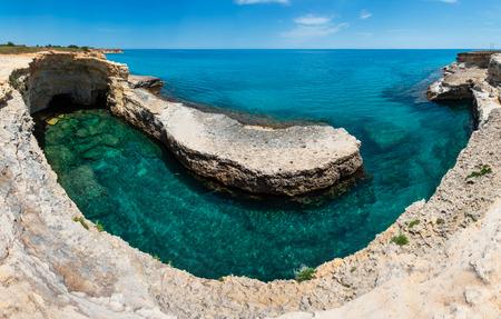 Picturesque seascape with white rocky cliffs, caves, sea bay and islets at Grotta del Canale, Sant'Andrea, Salento Adriatic sea coast, Puglia, Italy.