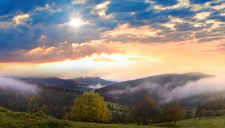 Misty morning and sunshine thru clouds in autumn Carpathian mountain, Ukraine. High resolution stitch panorama image.