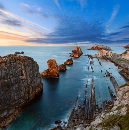 Atlantic ocean rocky coastline near Portio Beach (Pielagos, Cantabria, Spain) evening picturesque sunset view.