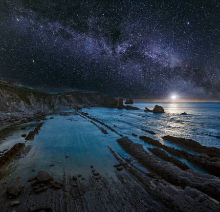 Arnia Beach (Spain) Atlantic Ocean coastline night view from rocky stones. Rising Moon and starry Milky Way in sky, and moonlight reflection in water.