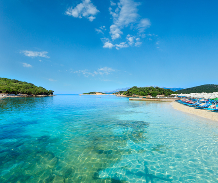 Beautiful Ionian Sea with clear turquoise water and morning summer coast view from beach (Ksamil, Albania). People unrecognizable.