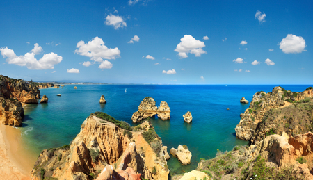 Ponta da Piedade (group of rock formations along coastline of Lagos town, Algarve, Portugal). People are unrecognizable. Two shots stitch panorama. Фото со стока