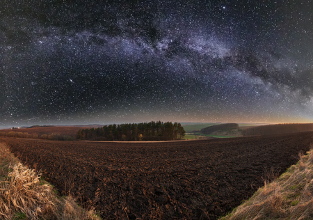Early spring night rural country landscape with plowed agricultural fields on hills, groves and village outskirts in far. Arable and growth farmlands and starry Milky Way in sky Stock fotó