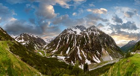 Paisaje al atardecer de montaña de los Alpes de verano con la carretera alpina y el río, Fluela Pass, Suiza