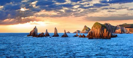 Sharp islets near Gueirua beach, Asturias, Spain. Sunset evening beautiful Atlantic ocean landscape. Multi shots high-resolution stitch panorama. 写真素材