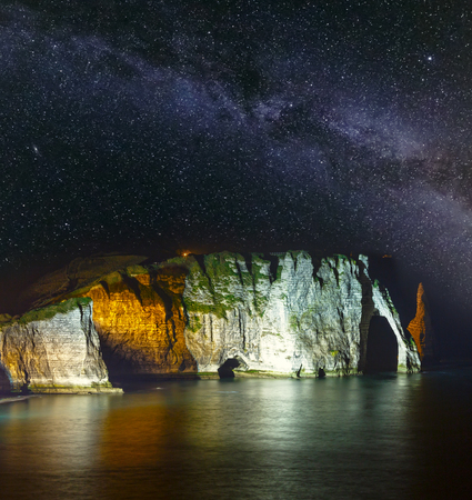 One of the three famous white cliffs known as the Falaise de Aval. Etretat, France. Night scene with starry Milky Way in sky and rocks illumination Archivio Fotografico