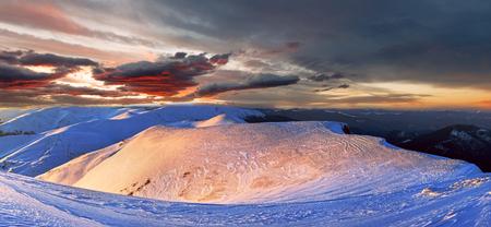 Mountain ridge sunset panorama in red colors view from last evening sunrays (Ukraine, Carpathian Mountains, Drahobrat ski resort). Multi shots stitch image.