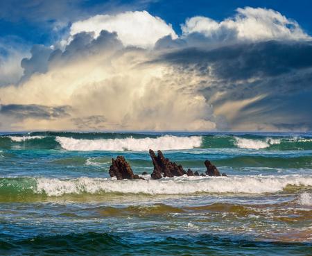 Olas de surf de mar y pequeñas rocas en el centro. Vista del paisaje marino desde la playa.
