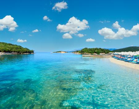 Schönes Ionisches Meer mit klarem türkisfarbenem Wasser und morgendlichem Sommerblick auf die Küste vom Strand, Ksamil, Albanien. Menschen nicht wiederzuerkennen.