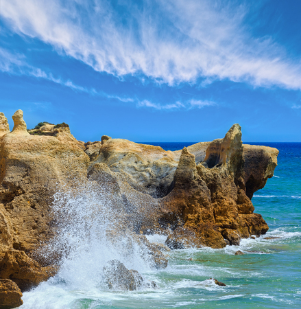 Summer Atlantic rocky coast view with splashes from waves, Albufeira outskirts, Algarve, Portugal