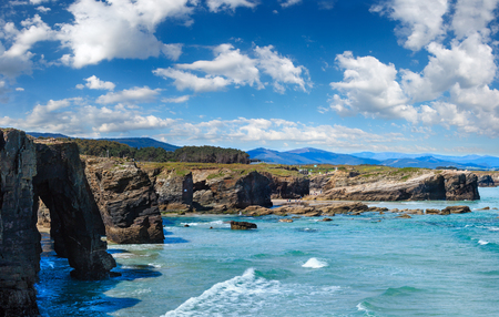 Natural rock arches on As Catedrais beach in low tide (Cantabric coast, Lugo, Galicia, Spain). Peoples are unrecognizable. Multi shots stitch high-resolution panorama. 写真素材