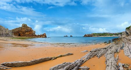 Arnia Beach, Spain. Summer Atlantic Ocean coastline with rock formations. Multi shots stitch panorama. 免版税图像