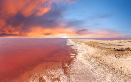 Red sunset above pink extremely salty Syvash Lake, colored by microalgae with crystalline salt depositions. Also known as Putrid Sea or Rotten Sea. Ukraine, Kherson Region. Archivio Fotografico
