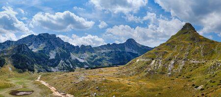 Picturesque summer mountain landscape of Durmitor National Park, Montenegro, Europe, Balkans Dinaric Alps, UNESCO World Heritage. Durmitor panoramic road, Sedlo pass. Cars unrecognizable.