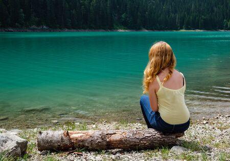 Young teenager girl rest on tree log on Black lake (Crno jezero) shore, summer landscape.  Zabljak Municipality, Montenegro. Stok Fotoğraf