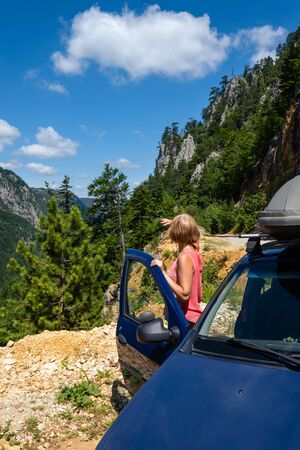 Woman near car is looking at picturesque summer mountain landscape of Tara Canyon in Durmitor National Park, Montenegro,  Balkans Dinaric Alps.