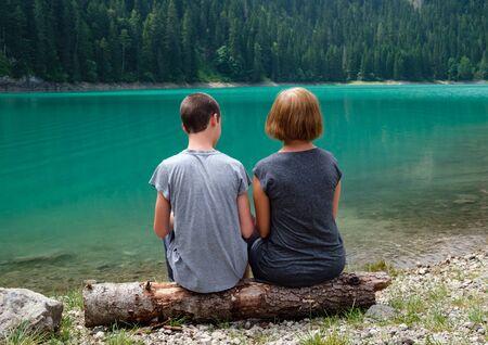 People, mother with son, rest on tree log on Black lake, Crno jezero, shore, summer landscape. Zabljak Municipality, Montenegro. Stok Fotoğraf