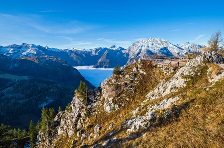 Autumn Alps mountain misty morning view from Jenner Viewing Platform, Schonau am Konigssee, Berchtesgaden national park, Bavaria, Germany.  Picturesque traveling, seasonal and nature beauty scene. Фото со стока - 139860713