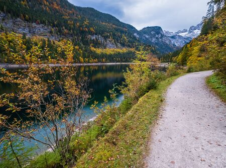 Gosauseen or Vorderer Gosausee lake, Upper Austria. Colorful autumn alpine view of mountain lake with clear transparent water and reflections. Dachstein summit and glacier in far.