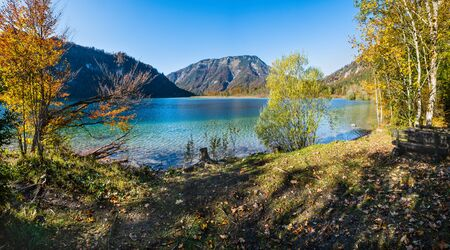 Sunny idyllic colorful autumn alpine view. Peaceful autumn Alps mountain lake with clear transparent water and reflections. Offensee lake, Salzkammergut, Upper Austria. Stockfoto