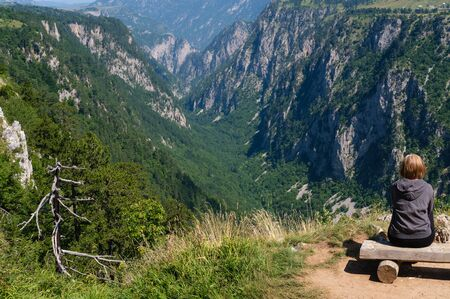 Woman on wooden bench over picturesque summer Tara Canyon in mountain Durmitor National Park