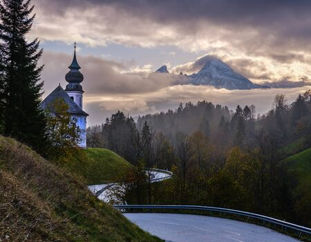 Overcast autumn morning in Bavaria with the small famous Maria Gern pilgrimage church (built in the current form 1708 - 1710) and mount Watzmann top silhouette through fog, Berchtesgaden, Germany