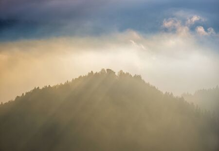 Autumn hazy day Berchtesgadener Land and mount Watzmann silhouette fragments in contra light cloudy view from Marxenhohe viewpoint, Bavarian prealps, Germany