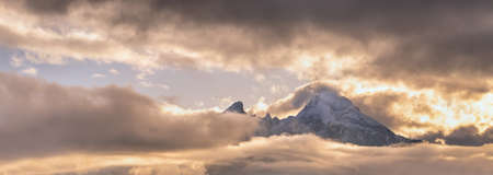 Foggy clouds and sunshine in evening overcast sky view. Famous Germany Alps Watzmann Mountain top silhouette in clouds. Natural weather and climate sky background scene. Stock Photo